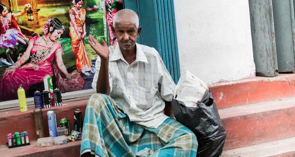 Indischer Straßenverkäufer vor Bollywood-Plakat