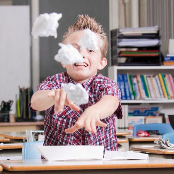 Kind wirft Papierbälle im Schulzimmer