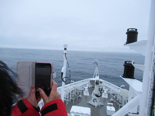 クジラの小さな点と、潮吹きがかすかに映る
