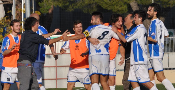 Emanuele Falone riceve l'abbraccio della panchina dopo il gol del vantaggio biancazurro
