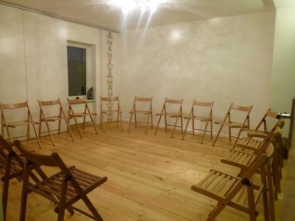 Bild vom großen Stuhlkreis: 14 Stühle und 1 Whiteboard. Die Mitte des Kreises ist individuell gestaltbar.