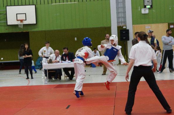 Zwei Kinder kämpfen auf einem Taekwondo-Turnier. Der Junge mit dem weißen Helm macht einen Sprungtritt gegen den Jungen mit dem blauen Helm.