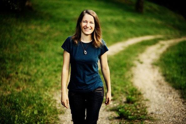 Portrait von Irene Arbeithuber, die auf einem Feldweg auf den Betrachter zugeht