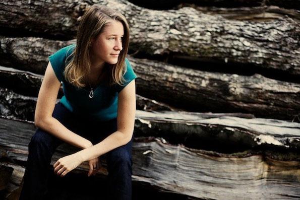 Portrait von Irene Arbeithuber auf einem Holzstoß sitzend