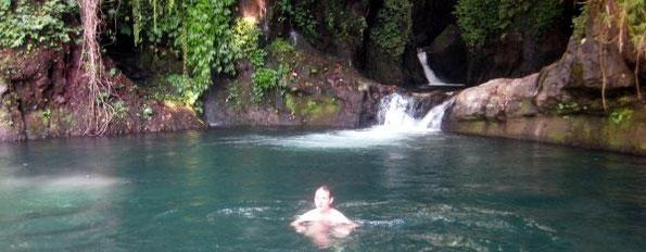 tourist, der in einem natürlichen flusspool vor grandioser fels- und naturkulisse schwimmt