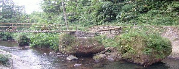 Bambusbrücke, die sich auf großen Felsbrocken abstützt