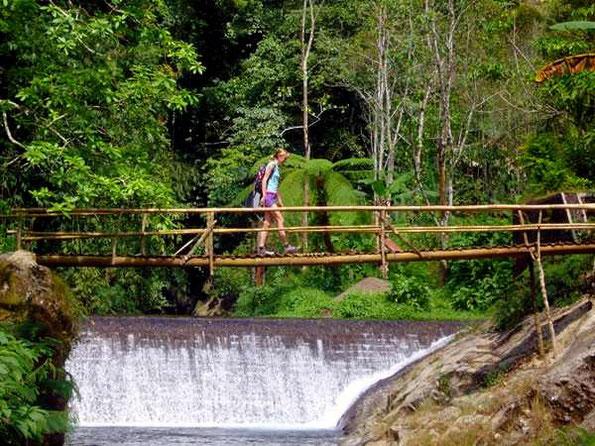 Touristin auf schwankender Bambusbrücke vor Wehr