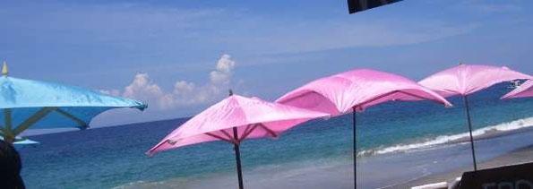 Sonnenschirme in pink und hellblau am Strand