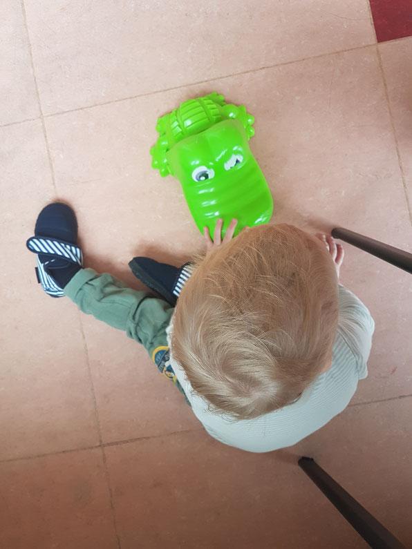 Kleinkind Junior spielt in der Kita mit einem Krokodil. Tagebuch über die Eingewöhnung auf Mama-Blog Patschehand.de.