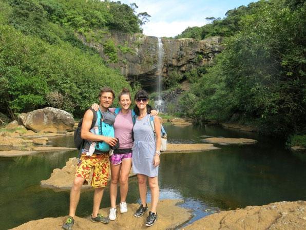 Glückliche Familie mit Tragepapa vor Wasserfall während der Elternzeit-Reise.