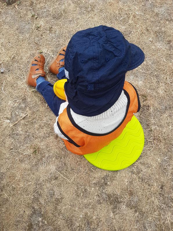 Kleinkind sitzt im Morgenkreis auf dem Hof seiner Berliner Kita. Erfahrungen rund um die Eingewöhnungszeit in der Kita auf Patschehand.de