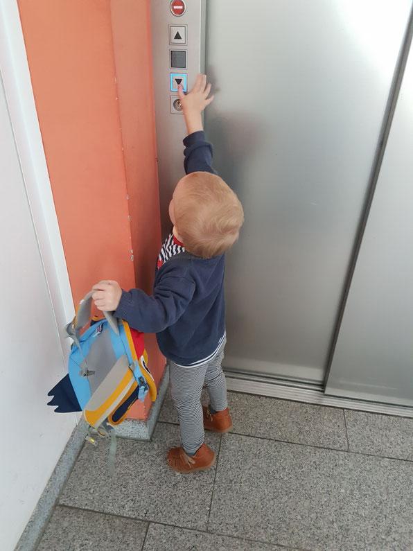 Kleinkind ruft den Fahrstuhl in Kita während der Eingewöhnungsphase.