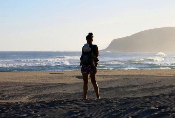 Glückliche Mutter mit Baby in der Trage am Strand während ihrer Elternzeit-Reise.