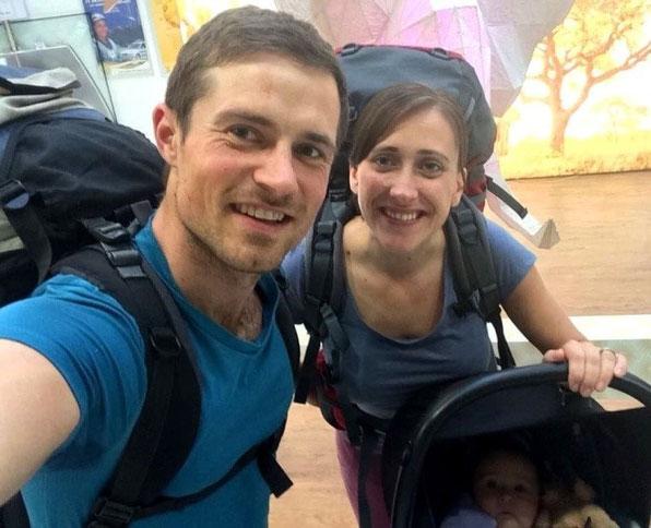 Junge Familie unternimmt während der Elternzeit die erste Reise mit Baby & lächelt am Flughafen in die Kamera.