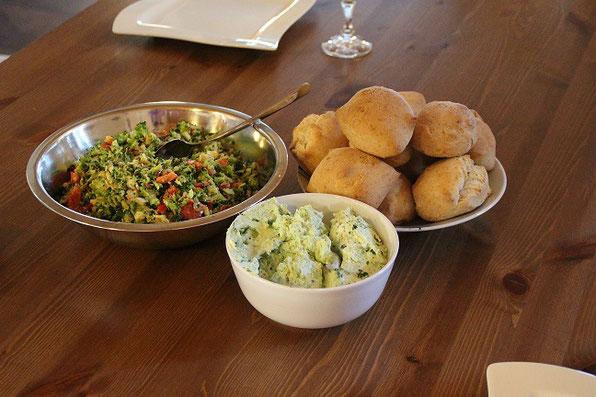 Die Vorspeise mit Dinkelbrötchen, Brokkolisalat und mediterranem Käseauftrich