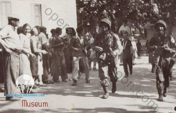Jean BIMA à gauche, pantalon clair et béret sur la célèbre photo des premiers parachutistes Américains du 517em qui entrent dans les Arcs au matin du 15 août 1944.