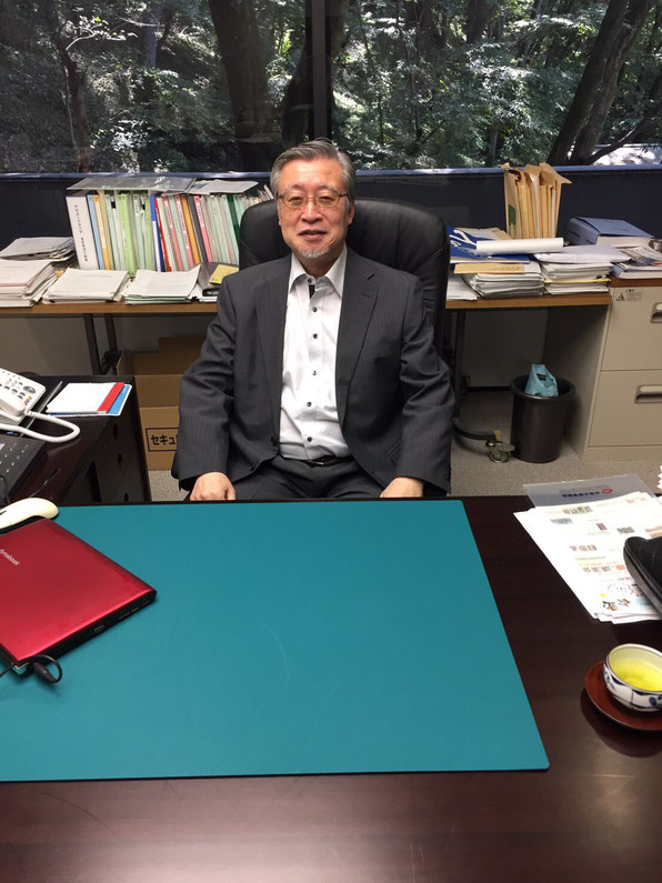 Omura poses for a photo during an interview with Hakumon Herald at his office.