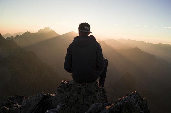 Jeune homme assis observe un paysage de montagnes