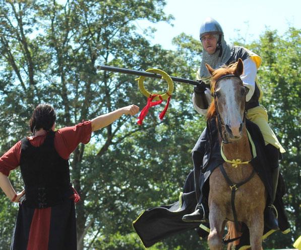 Un anneau est tenu par un écuyer. Les chevaliers doivent, avec leur lance, décrocher le plus d'anneaux possible en les enfilant par leur centre