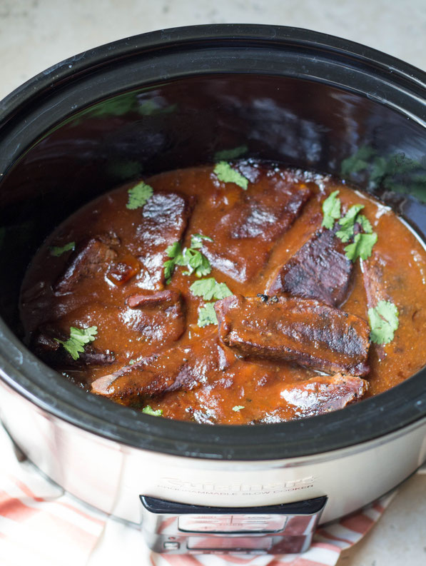 Indoor BBQ?  Yep!  These slow cooker BBQ beef ribs are super easy, and you can feed a crowd without doing much work at all! It's a great slow cooker recipe for the summer months.