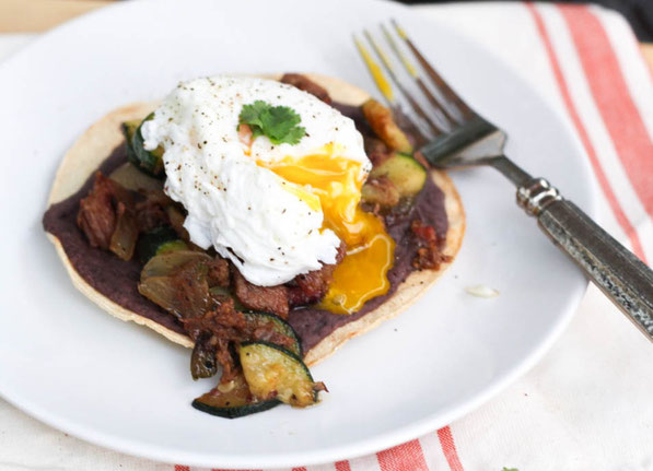 These tasty tostadas with beef, zucchini, black beans, and a poached egg are a tasty way to turn last night's beef dinner into a delicious high protein breakfast!