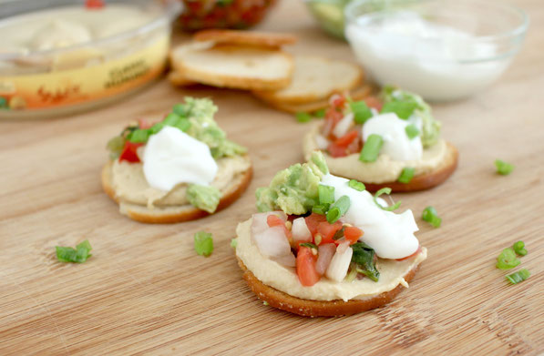 Quick hummus snack bites are the perfect semi-homemade healthy appetizer!  Store-bought hummus, avocado, pico de gallo, and Greek yogurt come together for this easy snack that people can assemble themselves at a party!