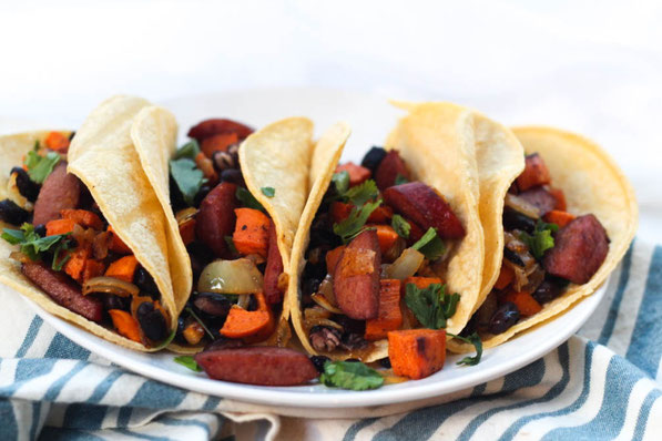Sausage, sweet potato, onions, and black beans roast together  beautifully on a baking sheet to create the base of these delicious  (and gluten free) one-pan tacos for two!