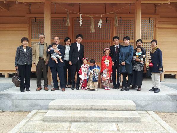 総社宮拝殿の前で記念撮影をする七五三のお参りに訪れた総勢14名のご家族