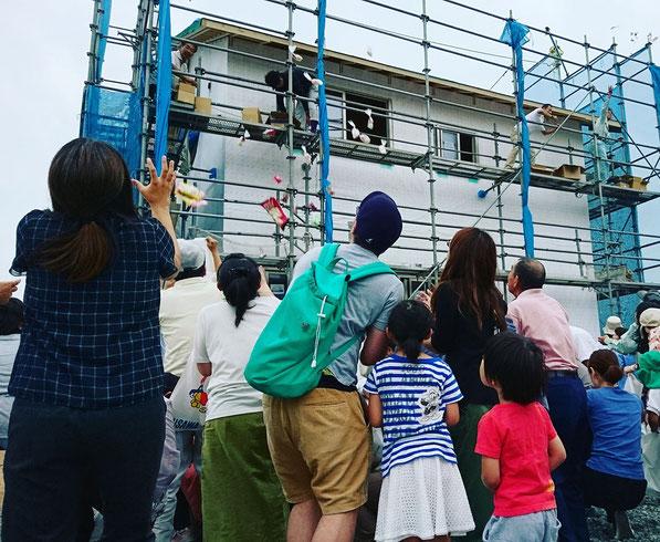 備前国総社宮が執り行う上棟祭にて2階部分から餅投げされた餅を取る人々