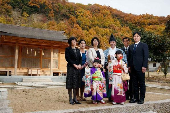 総社宮拝殿の前で記念撮影をする七五三のお参りに訪れたゆいちゃん、ゆきちゃん家族と武部宮司