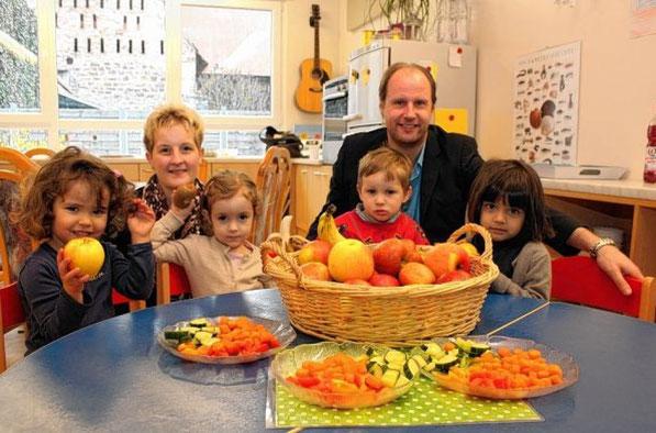 Die neue Leiterin Eva Eich (hinten links) und der Vorsitzende des Fördervereins, Dr. Christopher Brink (r.), freuen sich mit den Kindern über täglich frisches Obst.