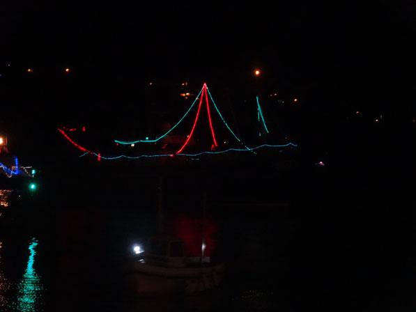 Ein mit Lichterketten dekoriertes Schiff auf dem Weg in den Hafen
