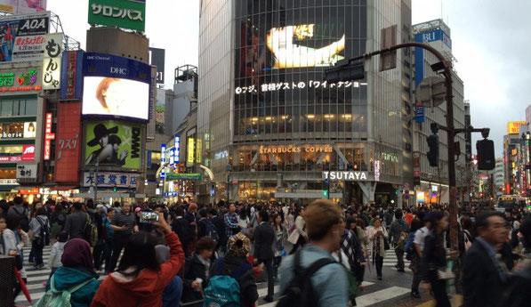 渋谷のスクランブル交差点で沢山の人が横断歩道を渡っている風景