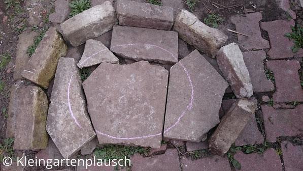 Fünf Bruchsteinplatten zum Halbkreis gelegt, umrandet von sieben Mauersteien
