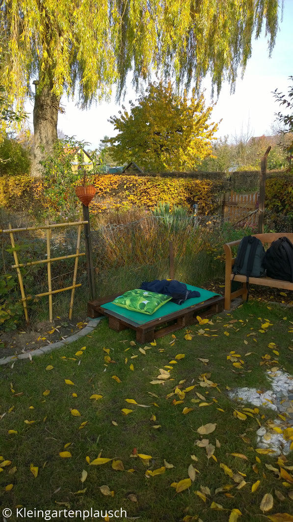 Braun lackierte Palette im Garten, obendrauf grüne Isomatte und grünes Kissen