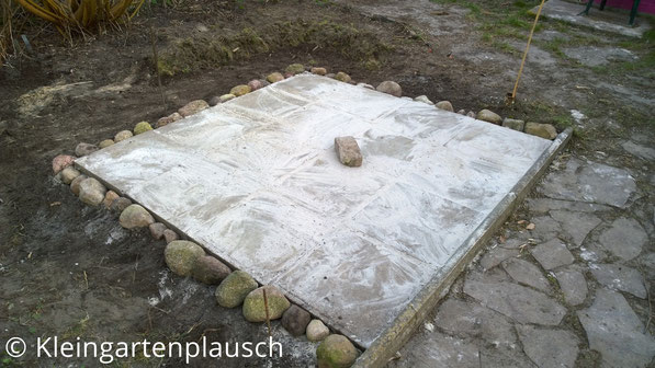 16 Waschbetonplatten im Quadrat verlegt, drumherum große Feldsteine