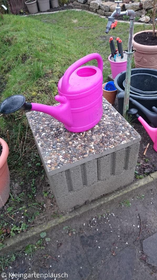 Je zwei Pflanzsteine übereinander mit Waschbetonplatte darauf bilden den neben dem Wasseranschluss gebauten Gießkannentisch, auf dem eine pinke Gießkanne steht.