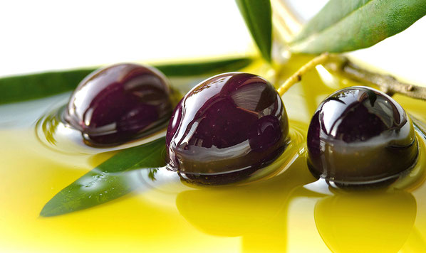 Bild: Frisch geerntete schwarze Oliven liegen in flüssigem Olivenöl