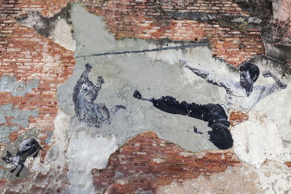 Ein Bild von Bruce Lee auf einer Mauer. Er vollführt einen Sprungtritt.