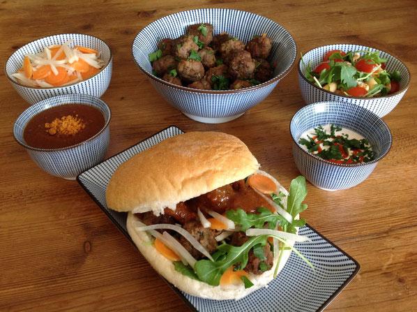 Vietnamese Bánh Mí met gehaktballetjes, zoetzure salade en sausjes.