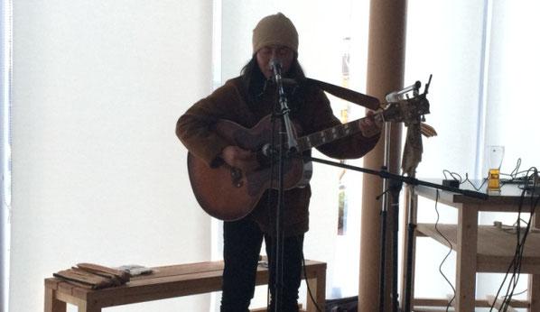 金丸 文武が品川Oursのステージでギターの弾き語りをしている場面