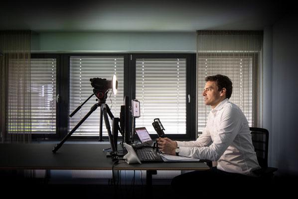Holger Sucker in abgedunkeltem Raum hält Live-Webinar