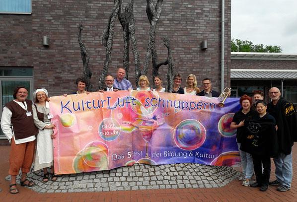 """Lächelnde Menschen, die das Fest der Bildung und Kultur veranstalten und besuchen stehen mit einem großen bunten Plakat  mit der Aufschrift """"Kulturluft schnuppern"""" draußen vor dem Gebäude des Landkreises Heidekreis."""