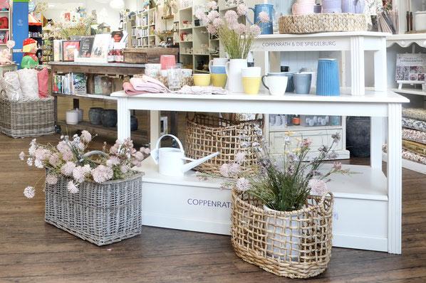Körbe mit Kunstblumen vor Regal mit Keramik