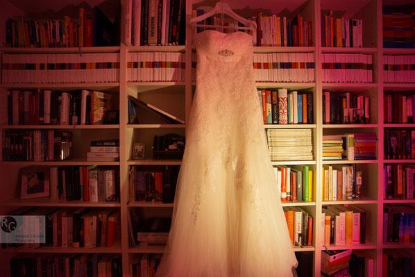 Hochzeitskleid hängt am Bücherschrank beim Getting Ready Shooting durch den Hochzeitsfotograf Gelnhausen und Hanau.