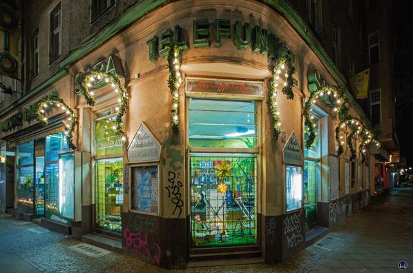 Musikhaus Bading in Berlin - Neukölln, Karl - Marx - Straße. Die Fassadenecke der Musikalienhandlung in Weihnachtsbeleuchtung