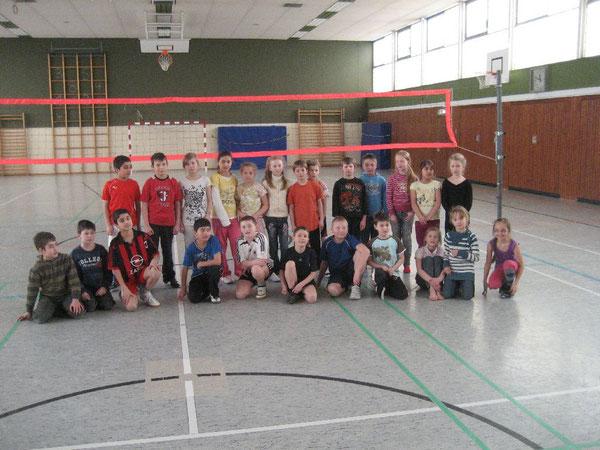 Mädchen und Jungen spielen im Volleyball kameradschaftlich zusammen