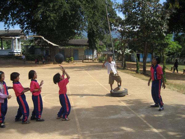 Chiang Mai: Ein Mädchen aus der 1. Klasse prtischt den Willeball ohne Angst. Und: Mit einfachen Mittel wird mit einem Autoreifen ein Volleyballständer gebaut.