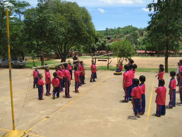 Dorfidylle: Jungen und Mädchen spielen gemeinsam auf dem Schulhof Volleyball