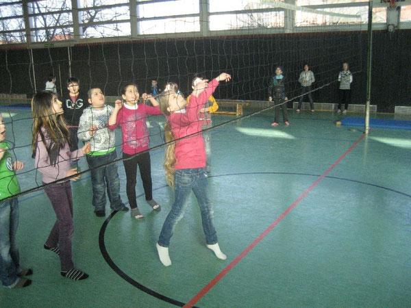 Gebannt schauen die Mitspieleinnen zu, wie der Ball über das Netz gepritscht wird